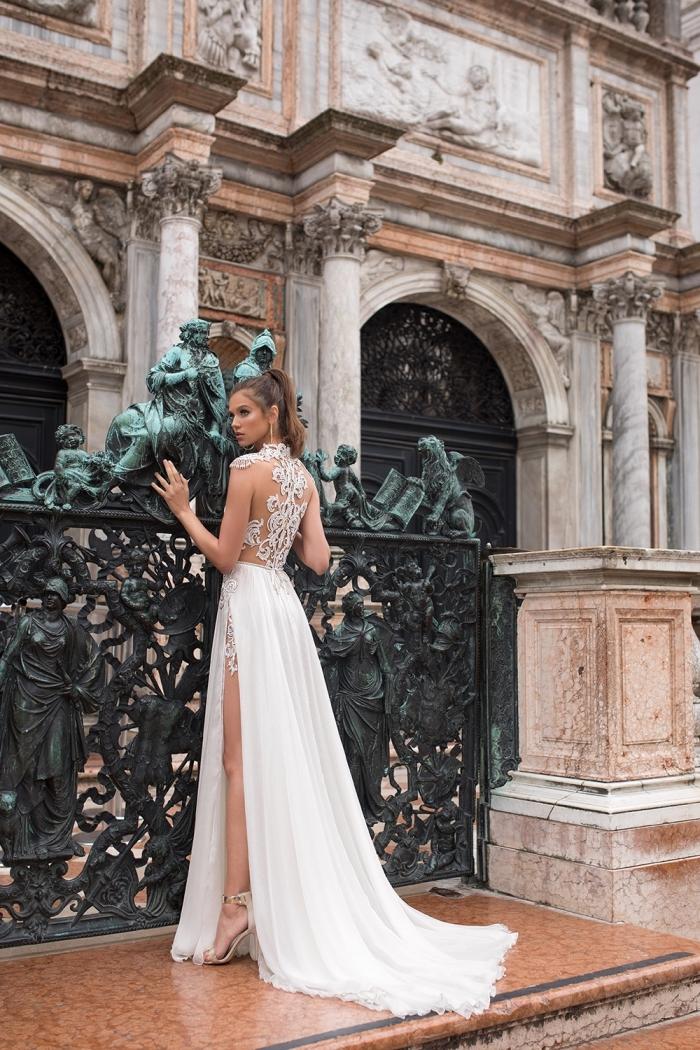 robe de cérémonie femme pour mariage avec dos en dentelle et traîne, vision romantique de mariée aux cheveux attachés en queue de cheval haut