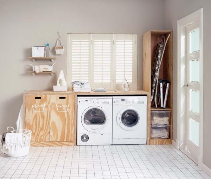 pièce spacieuse aux murs beige avec carrelage de plancher blanc et meubles de bois clair, petite etagere buanderie de bois clair