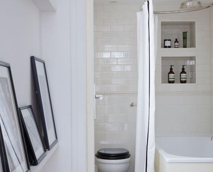 decoration petite salle de bain blanche avec baignoire blanc, niche murale rangement, wc noir et blanc et deco cadres graphiques
