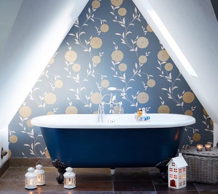 petite salle de bain design sous pente, mur décoré d un papier peint fleuri, baignoire bleu marine et carrelage sol marron foncé, deco de lanternes