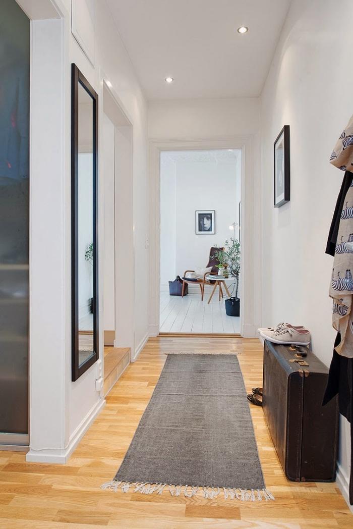 modèle de deco couloir aux murs blancs avec éclairage led et plancher de bois clair, miroir rectangulaire à cadre noir