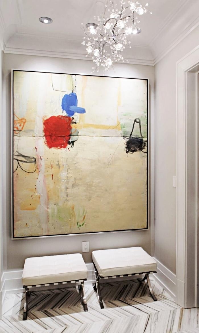 modèle de deco entree en blanc avec grande peinture art abstraits et deux tabourets bas en beige, modèle de luminaire en verre
