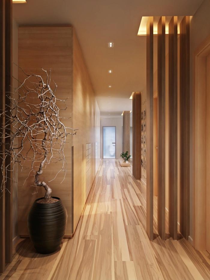 tendance déco intérieur moderne et chaleureux avec meubles et revêtement murs et sol en bois clair, plantes vertes et arbre séché dans un pot noir