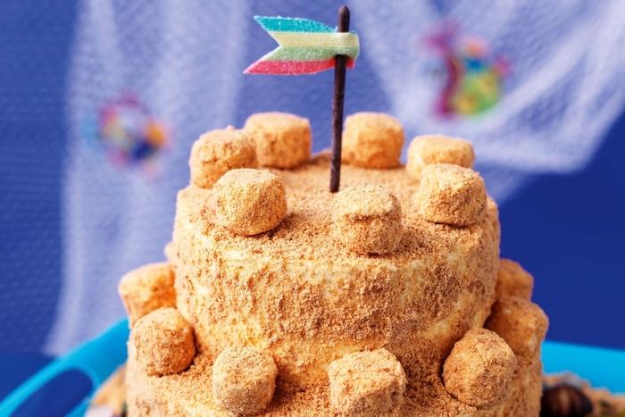 recette de gateau d'anniversaire chateau de sable à deux étages décoré de fanion en bande acidulée