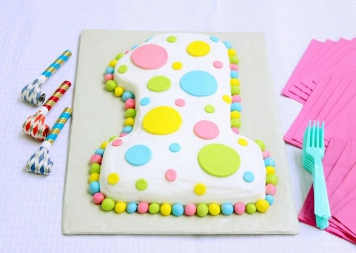 gateau anniversaire 1 an en forme de chiffre recouvert de glaçage blanc et de ronds colorés en pâte à sucre