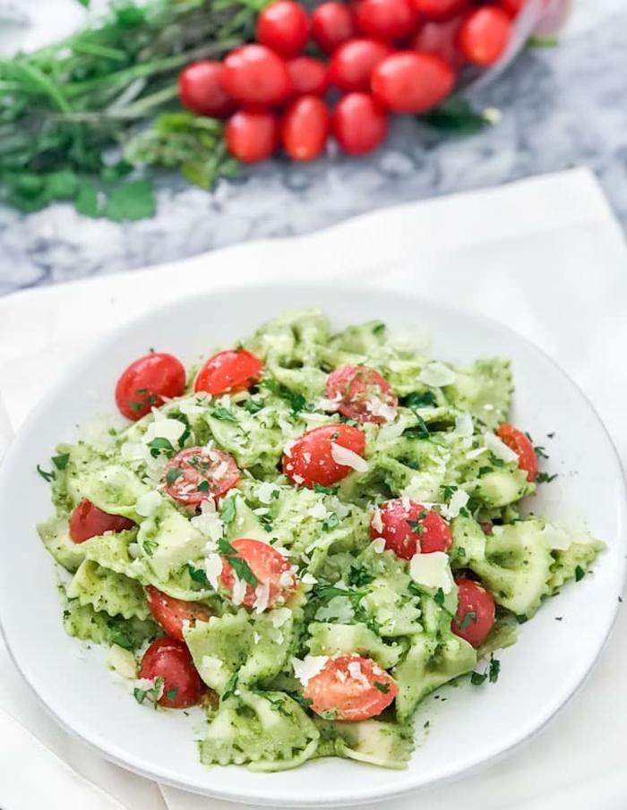 repas dietetique, pasta farfalle avec pesto d'olives vertes, des tomates cherry, du persil, une recette fraîcheur pour un menu de régime