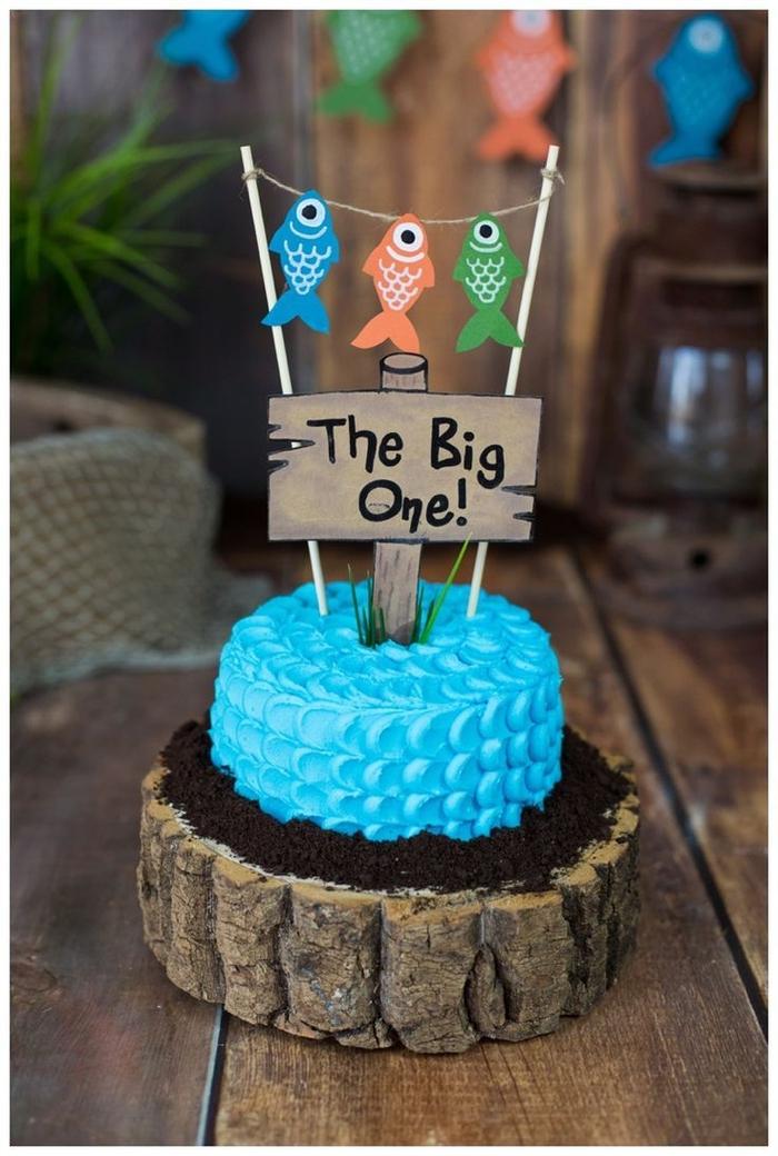un gateau anniversaire 1 an facile recouvert de glaçage bleu façon écailles de poisson, présenté sur un rondin de bois