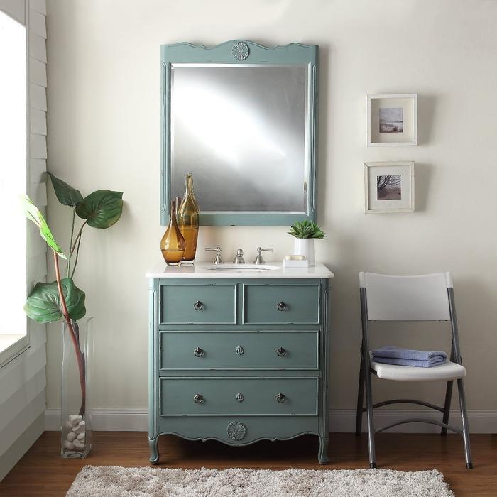 ambiance apaisante et zen dans une salle de bain ancienne équipé d'un meuble-vasque vintage bleu paon assorti avec un miroir ancien