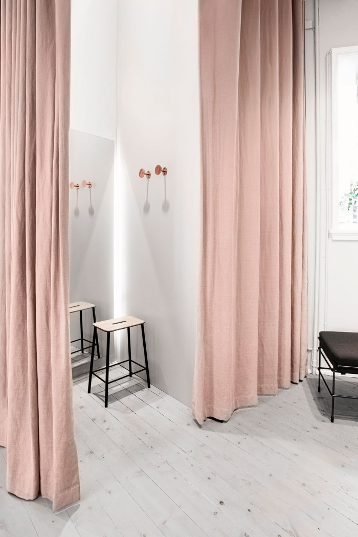 décoration d'intérieur moderne aux murs blancs avec rideaux longs de couleur rose poudré et tabouret en bois et noir mate