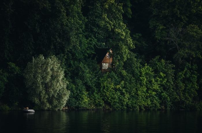 maison de bois à deux étages construite dans la forêt au-dessus d'un lac, bateau dans eau qui reflète les arbres vertes