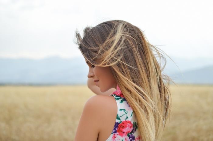exemple de balayage blond sur cheveux longs raids de base châtain clair, modèle de robe blanche aux motifs floraux rose et vert