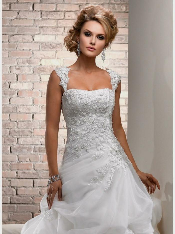 jolie robe de mariée, robe boheme mariage, coiffure chignon sophistiqué, mur en briques
