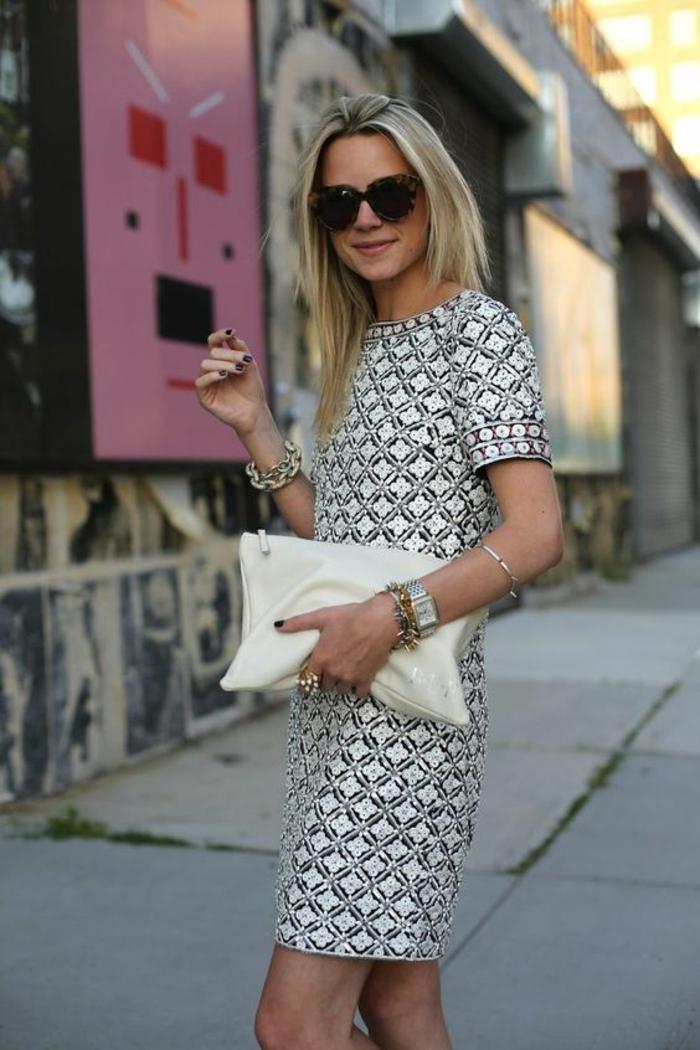robe en blanc avec des motifs losanges noirs, manches courtes, tenue décontractée femme, grand sac pochette couleur ivoire, tenue de soirée femme