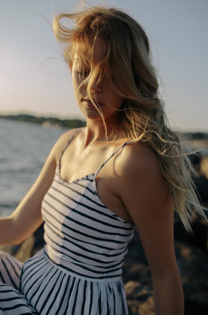 jeune femme aux cheveux longs ombrés de couleur blond foncé et blond caramel, modèle de robe marine rayée