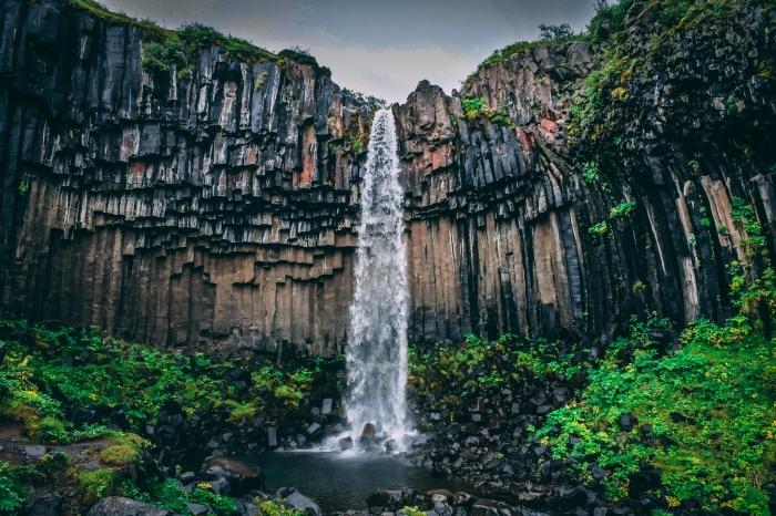 photo de chute d'eau gigantesque avec rochers et plantes vertes sur les pierres noires, fond d écran wallpaper avec chute d'eau