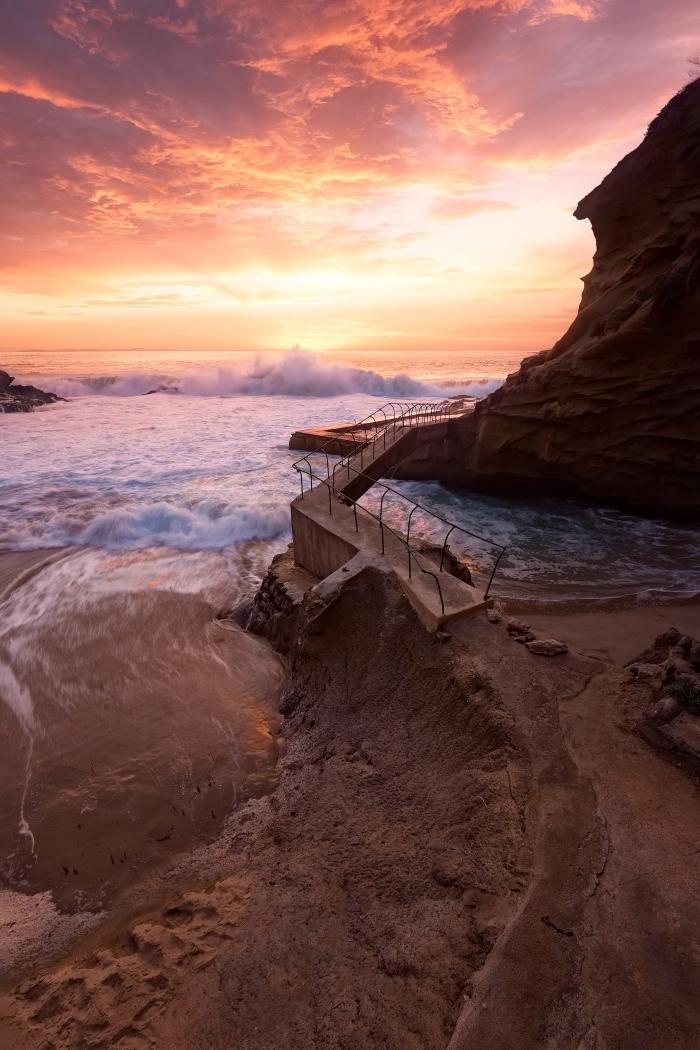 choisir un wallpaper fond d écran naturel, photo de l'océan dont les vagues se brisent dans les rochers au lever du soleil
