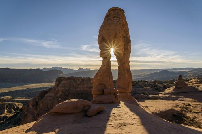 formations de pierres beiges au sommet d'un paysage désertique, paysage paradisiaque, soleil qui s'infiltre a travers un trou dans la pierre