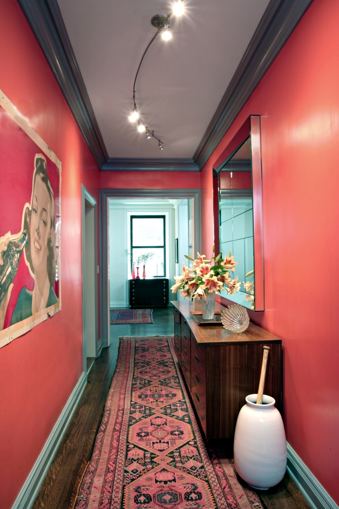 modèle de deco hall entrée aux murs rouge avec plafond blanc en bordure foncé et plancher de bois marron
