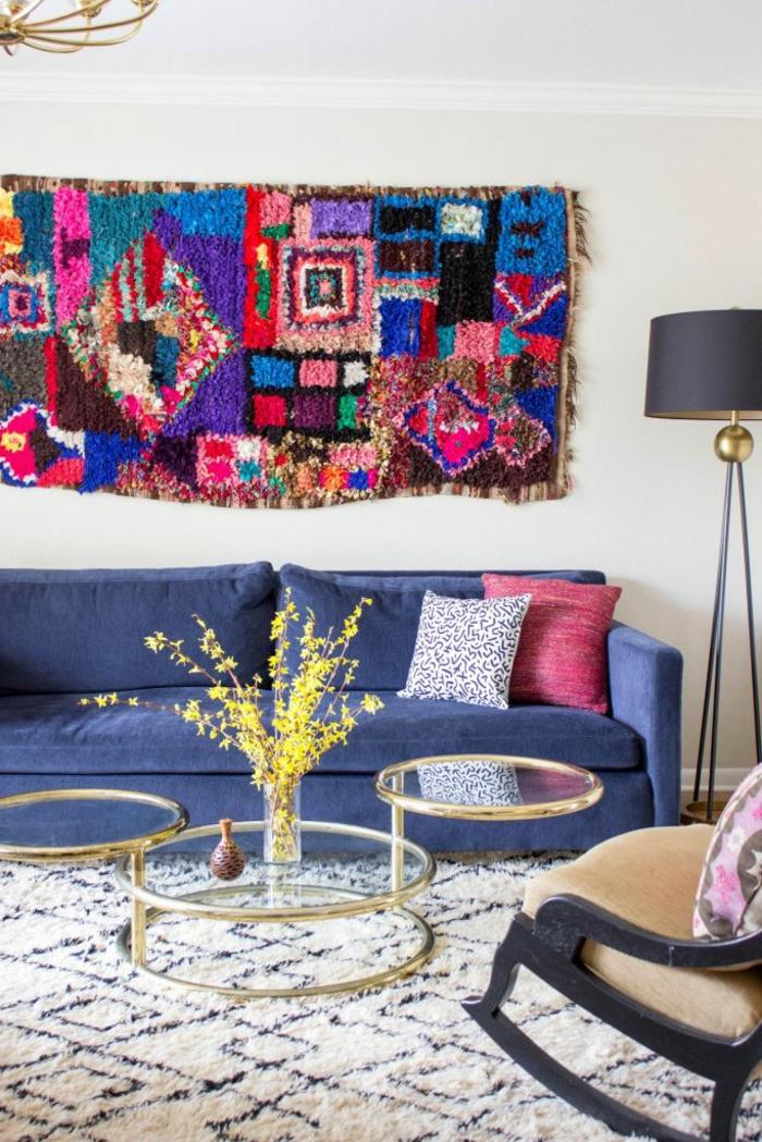 tenture murale en couleurs chaleureuses, tables rondes en verre et métal, chaise berçante, deco orientale