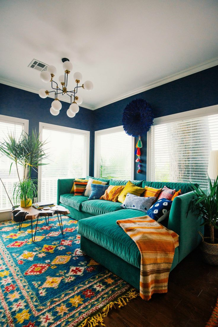 tapis boheme en jolies couleurs, grand canapé d'angle vert émeraude, plafond blanc, plafonnier contemporain, grandes fenêtres