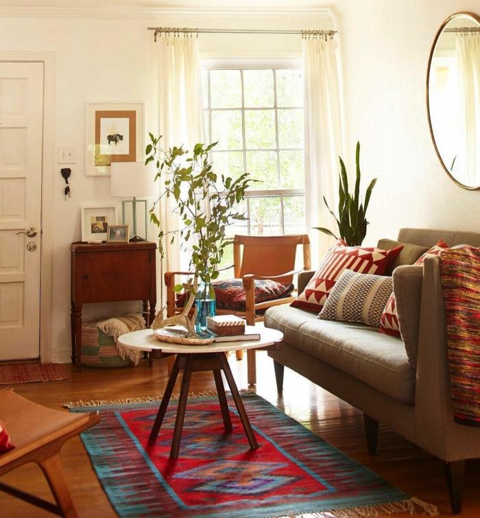 miroir ovale, séjour ethnique, table ronde, petit buffet en bois, peinture murale blanche