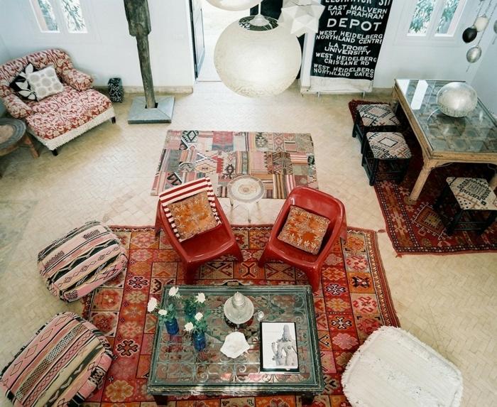 table en verre, poufs bariolés style boho chic, trois tapis ethniques, lampe suspendue blanche, table avec tabourets