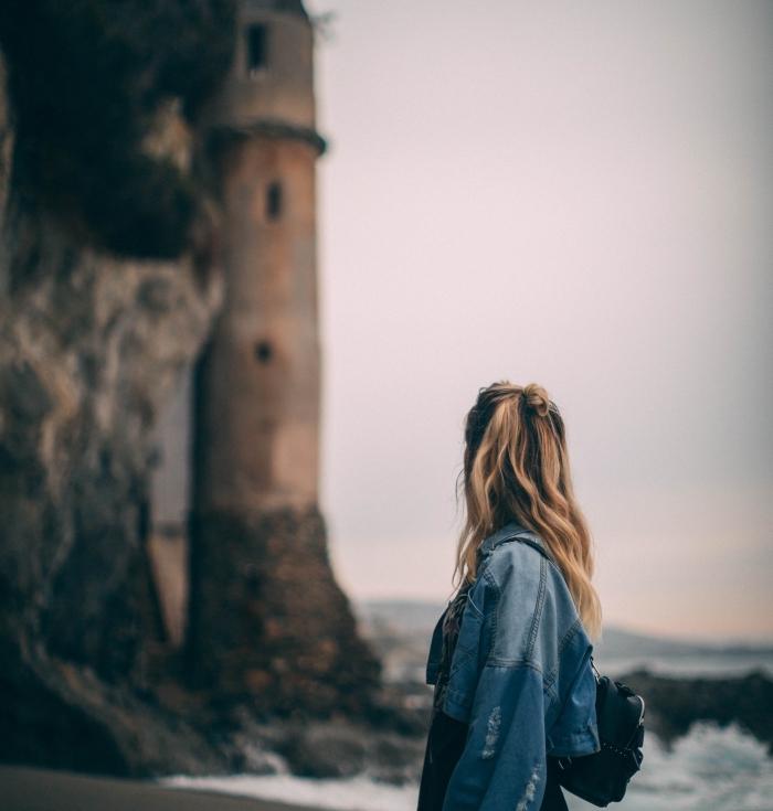 coiffure romantique de style naturel aux cheveux mi-attachés en demi bun, combiner le sac à dos cuir noir avec veste en denim