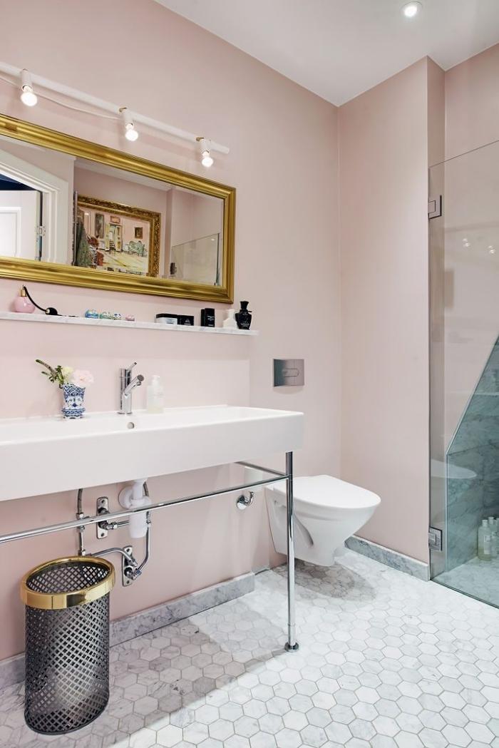 décoration de la salle de bain aux murs rose pâle et plafond blanc, modèle de miroir rectangulaire en or avec éclairage industriel