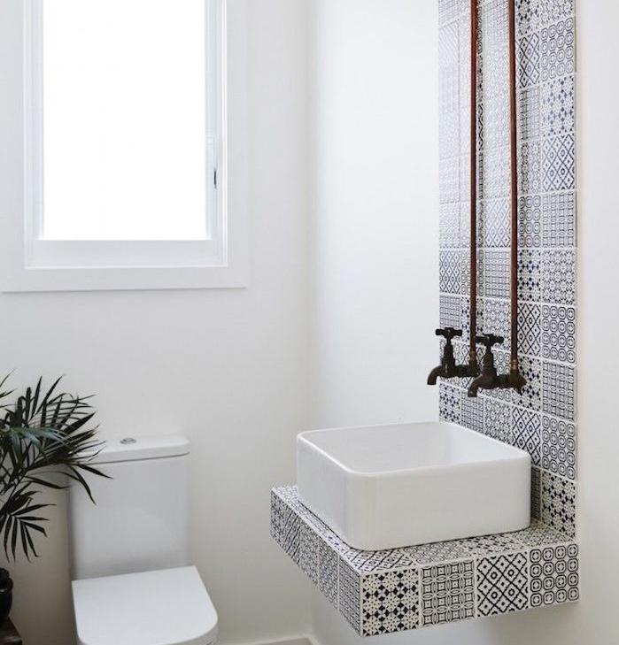 petite salle de bain design avec vasque blanc et carrelage bande noir et blanc, wc et murs blancs