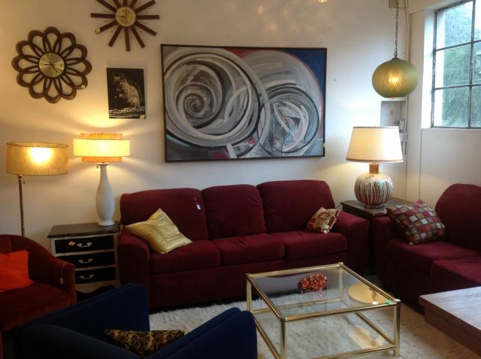 couleur bordeau, table basse en verre, sofas en rouge et bleu, lampes de table et lampe suspendue