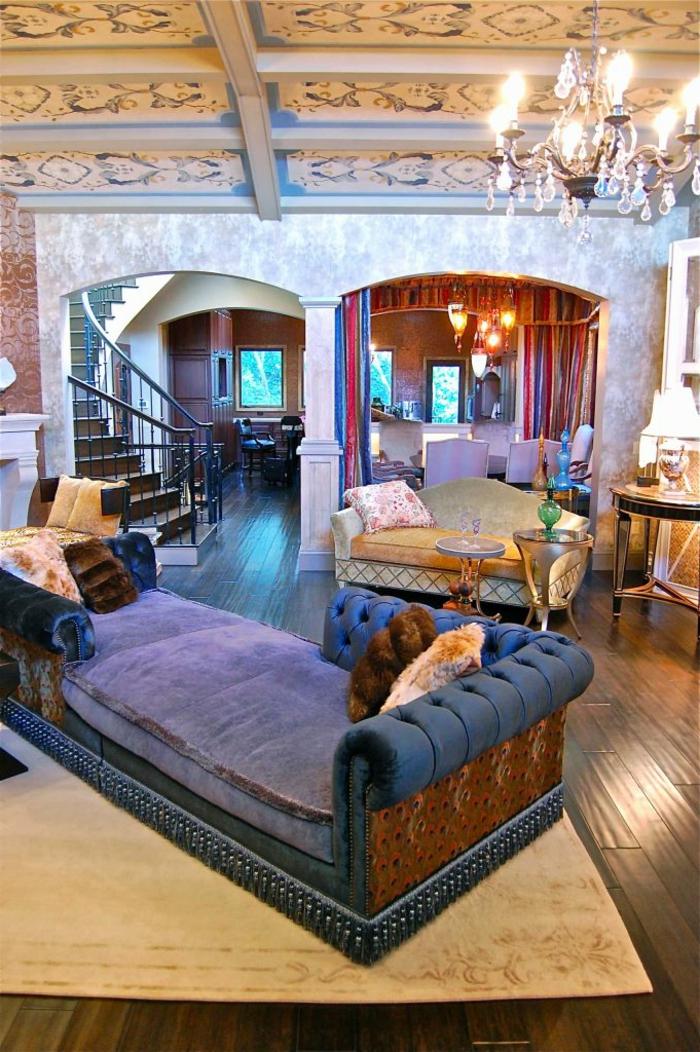 escalier tournant, grand sofa moelleux en bleu, chandelier pampilles, grande maison à plan ouvert