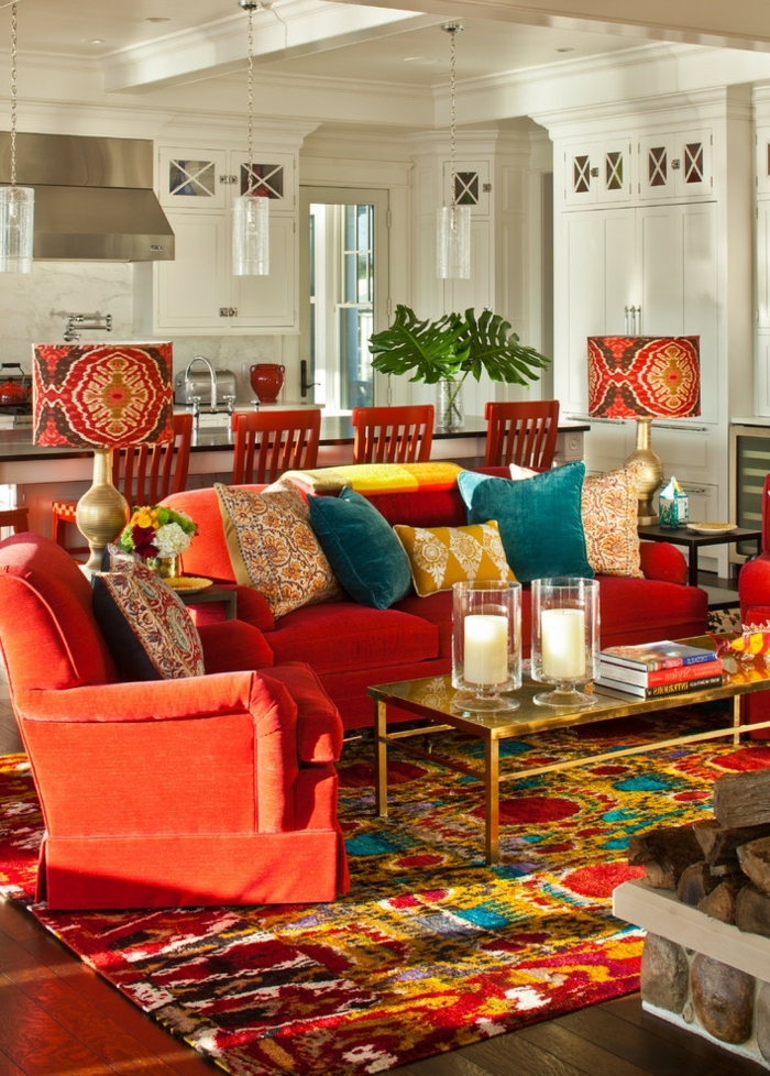 tapis en couleurs radiantes, table en verre et cadre doré, grand sofa rouge