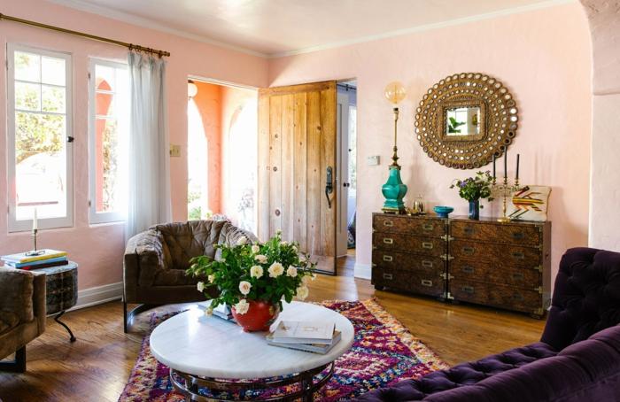 peinture murale rose, table ronde blanche, miroir décoratif, tapis en couleurs ethniques
