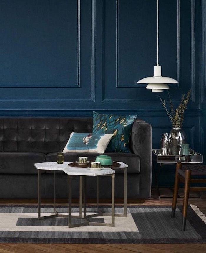 salon décoré avec murs peints en bleu pétrole, canapé gris anthracite rétro