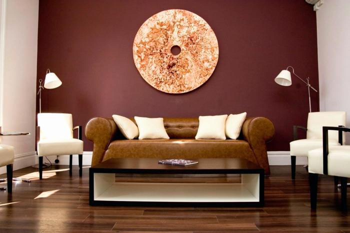 sol en bois, table bassen canapé marron avec coussins crème, quatre chaises élégantes
