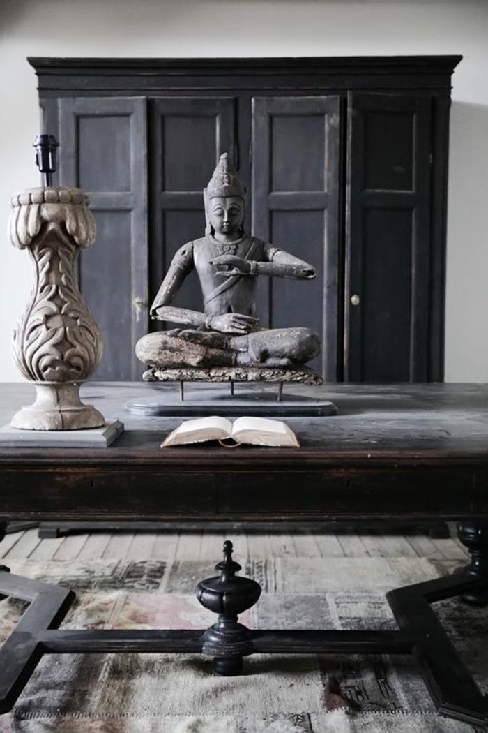 feng shui salon, grande table en marron foncé, parquet en nuances foncées, meuble de rangement en noir dans une niche dans le mur avec des portes aux poignées rondes