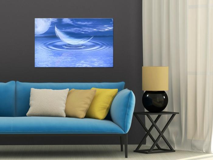 feng shui salon avec canapé en bleu pastel avec des coussins en jaune, beige et blanc, panneau décoratif en bleu et blanc avec une plume qui tombe dans l'eau, table carrée en fer forgé, couleur noire, rideaux blancs, sol recouvert de parquet gris