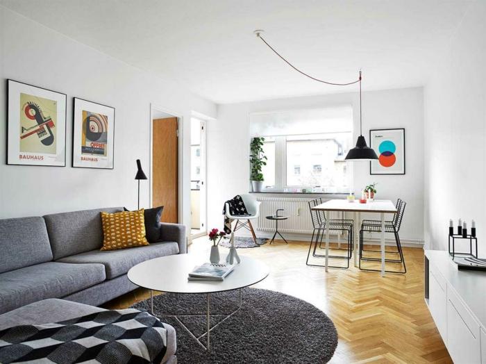 deco epuree, deco salon zen, canapé gris, trois tableaux avec des cadres noirs et des motifs graphiques, tapis rond en gris fumée, table de salle a manger en blanc avec quatre chaises en métal noir