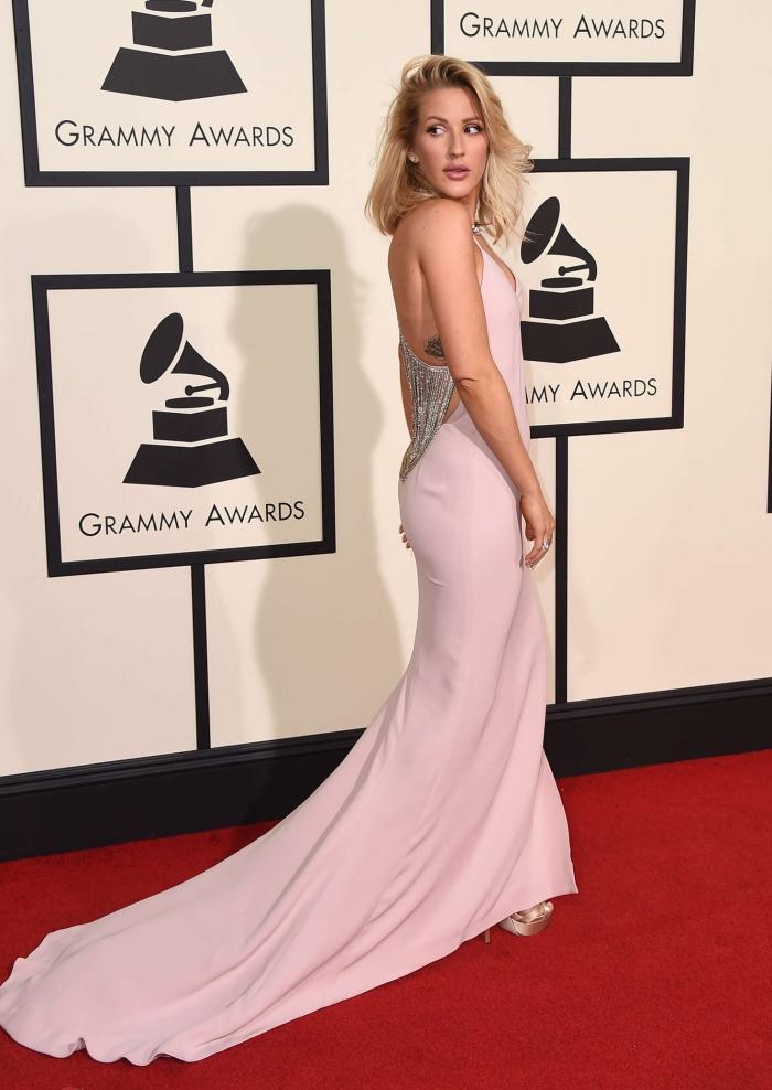 Ellie Goulding en robe rose pastel longue avec traîne et décoration bijou sur le dos, coupe de cheveux mi-longs avec frange de côté