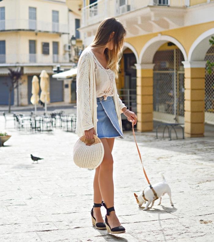 jolie femme habillée en jupe courte de denim combiné avec débardeur beige et gilet en crochet motifs floraux, coiffure de cheveux longs ombré