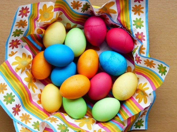 exemple d'oeufs colorés pour paques avec peinture alimentaire et cuillère de vinaigre arrangés sur une assiette couverte de serviette multicolore