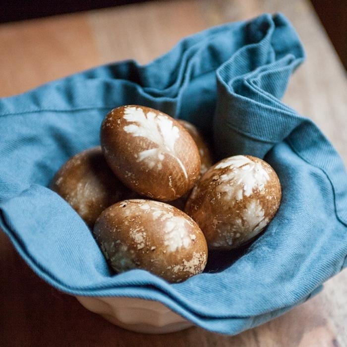 panier céramique blanc avec serviette bleu et oeufs colorés en marron aux empreintes végétales blanches