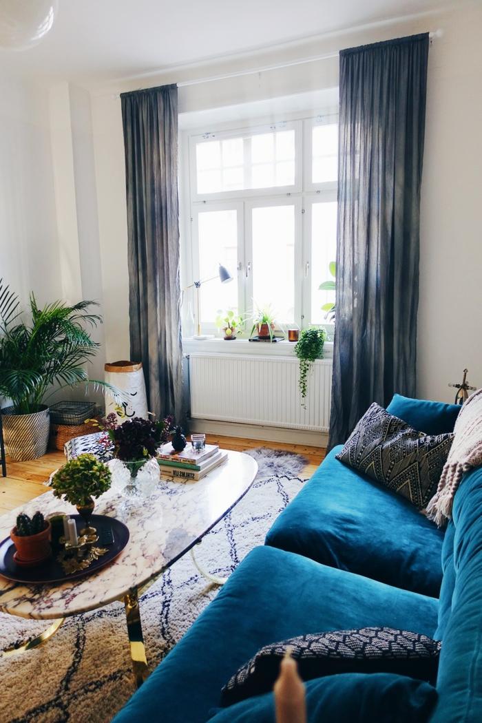 peinture murale blanche, grande fenêtre, rideau noirs, tapis berbère, coussins géométriques