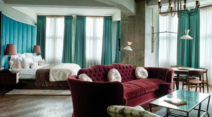 grand sofa couleur rouge bordeaux, rideaux bleus, plafonnier design brut