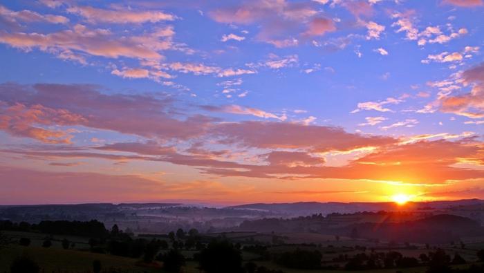 paysage d'un ciel en pourpre, soleil orange au-dessus d'une plaine, petit village de Toscane, plantations d'oliviers, ambiance paisible du soir