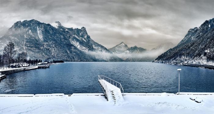 fond ecran ordinateur avec photo de nature hivernale au ciel gris, photo de lac et montagnes enneigées avec brouillard