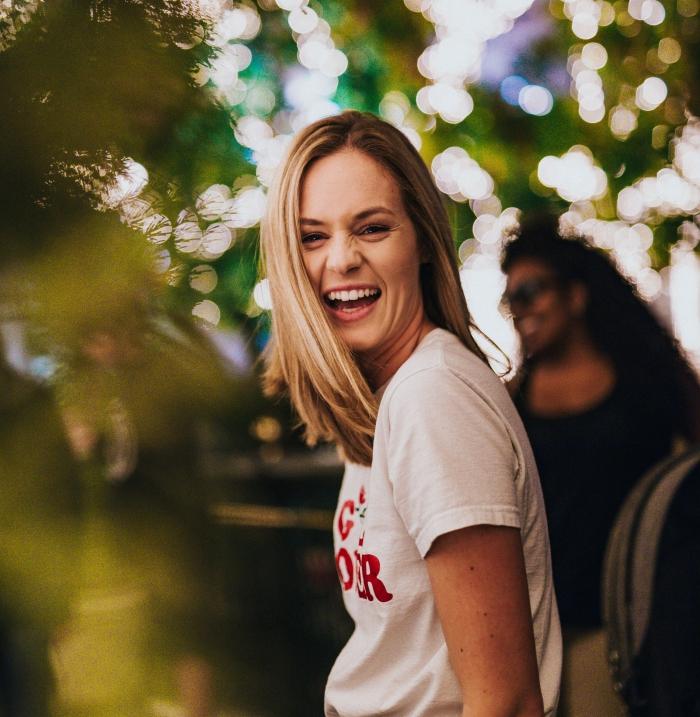 jolie femme en coiffure ombrage cheveux longs de base châtain foncé avec mèches blondes, modèle de t-shirt blanc avec lettres rouges
