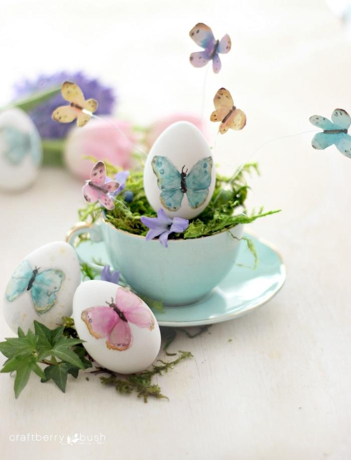 arrangement de table de paques avec service de thé de nuance turquoise et oeuf à coquille blanche décoré de papillons