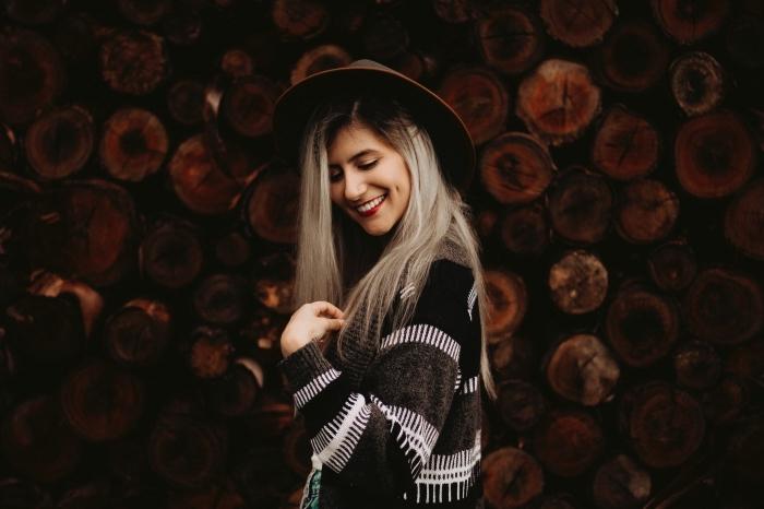 jolie coiffure aux cheveux longs et raids avec racines foncées et pointes blond gris, tenue boho chic en gilet et capeline foncés