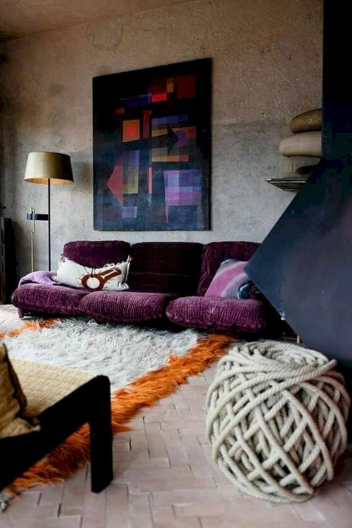 salon spacieux, pouf en gros fils de laine, peinture abstraite au mur, lampe de sol, sofa pourpre